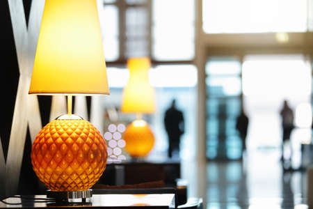 Reception area in luxury hotel close up on lamp with people traveling in and out the front entrance