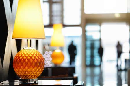 Receptie in het luxe hotel close-up op lamp met mensen die reizen in en uit de vooringang