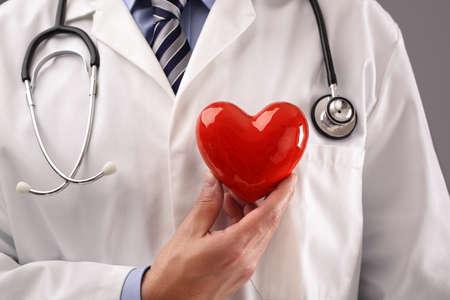Medico o cardiologo tenendo il cuore contro il concetto di petto per l'assistenza sanitaria e la diagnosi medica prova a impulsi cardiaci Archivio Fotografico