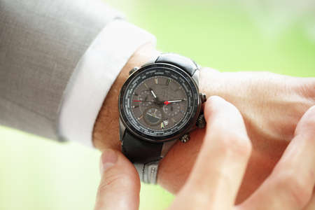wrist watch: Businessman checking the time on his wrist watch concept for urgency, deadline or running late
