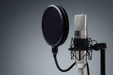 microfono de radio: Micr�fono del estudio y el escudo pop en soporte de micr�fono contra el fondo gris