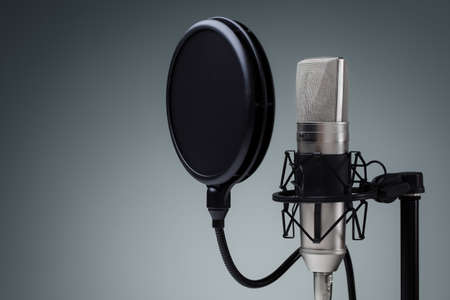 mike: Studio microphone and pop shield on mic stand against gray background Stock Photo