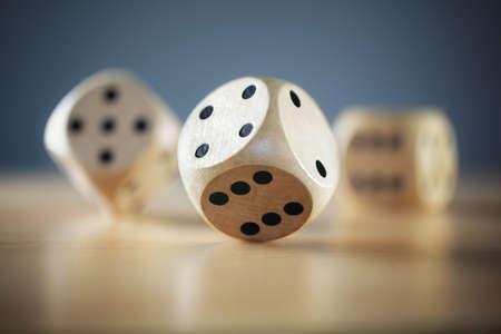 Rolling drie dobbelstenen op een houten bureau