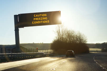 icey: Motorway gantry sign in early morning winter sunshine reading caution freezing conditions