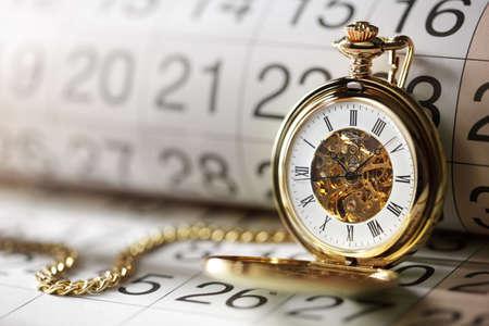 Reloj de bolsillo contra un calendario concepto de la planificación o programación Foto de archivo - 35905416