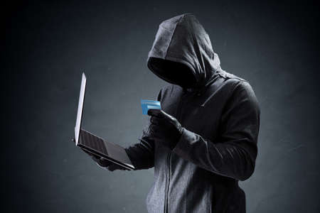 internet fraud: Computer hacker with credit card stealing data from a laptop concept for network security, identity theft and computer crime