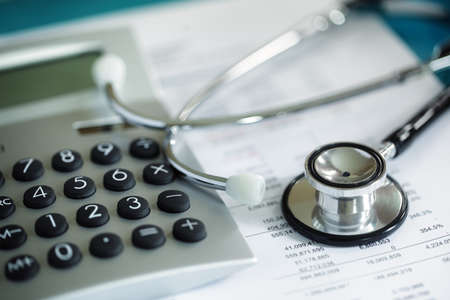 Calculator and stethoscope on financial statement concept for finance health check or cost of healthcare Standard-Bild