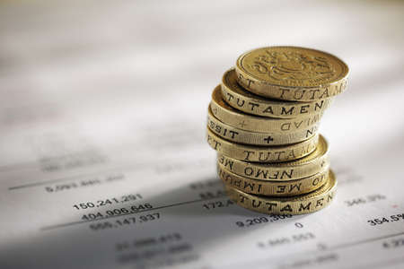 balance: Stack of pound coins on financial figures balance sheet