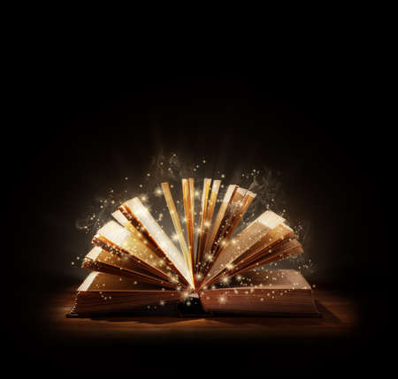 books: The magic of reading, storytelling and education or bible and religion, Black backround space above for text message or copy. Stock Photo