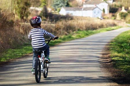 niños en bicicleta: Andar en bicicleta en un camino rural concepto de estilo de vida saludable, hacer ejercicio y la seguridad vial