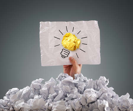 hardship: Businessman buried under crumpled pile of papers with an idea sign Stock Photo