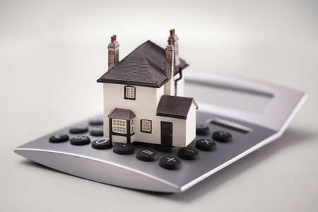 House resting on calculator concept for mortgage calculator, home finances or saving for a house