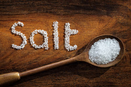 Sea salt on wooden spoon and the word salt written in grain