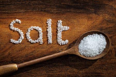 sal: La sal del mar en la cuchara de madera y la palabra escrita en la sal de grano
