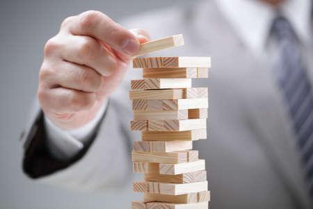 Planning, risico en strategie in het bedrijfsleven, zakenman gokken plaatsen van houten blok op een toren
