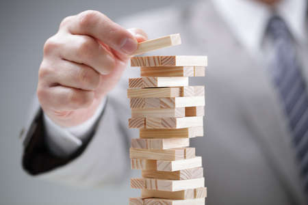 business success: Planning, risk and strategy in business, businessman gambling placing wooden block on a tower