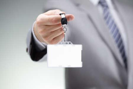 De negocios que muestra una tarjeta de identificación de identidad en blanco en una cuerda de seguridad Foto de archivo