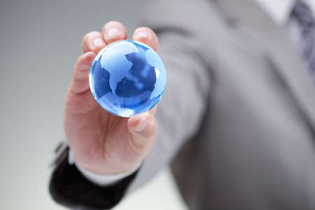 businessman carrying a globe: Business man holding a blue globe in his hand symbol for global business, communications or environmental conservation Stock Photo