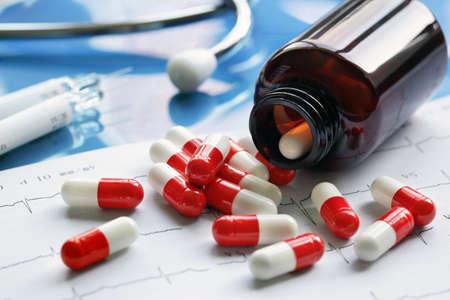 drogadiccion: Prescripción botella de medicina píldora y la jeringa en copia impresa cardiograma Foto de archivo