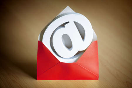 email contact: E-mail@ at symbol inside a red envelope on a desk Stock Photo