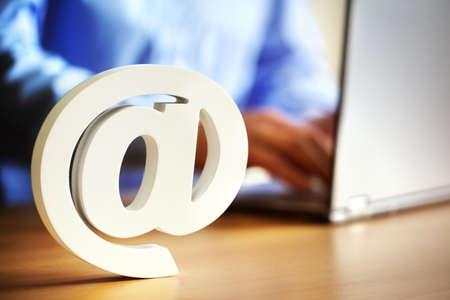 correo electronico: E-mail @ en el s�mbolo en un escritorio de oficina con el hombre en la computadora port�til Foto de archivo