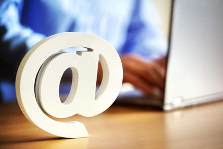 E-mail @ at symbol on an office desk with man on laptop computer