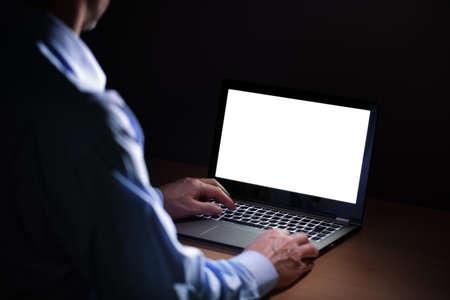 using the computer: Tarde en la noche la adicción a Internet o trabajando hombre finales usando la computadora portátil en un escritorio en la oscuridad
