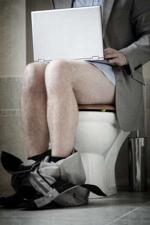 work addicted: Businessman working on laptop while sitting on toilet concepts for urgent deadline, working from home, workaholic and internet addiction