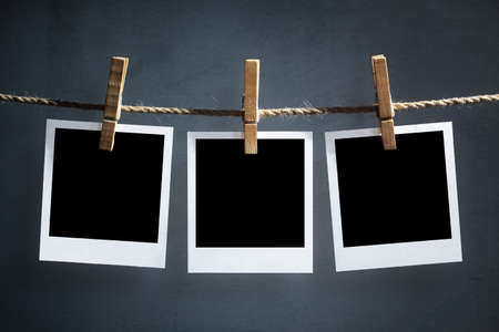 Blank instant print transfer photographs hanging on a clothesline Stock Photo