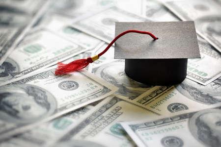 educação: Tampão da graduação da placa do almofariz em cem notas de dólar conceito para o custo de uma educação universitária e universitária
