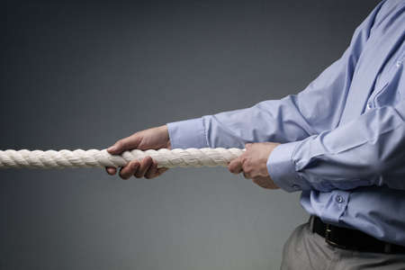 Businessmen pulling tug of war with a rope concept for business competition, rivalry, challenge or dispute photo