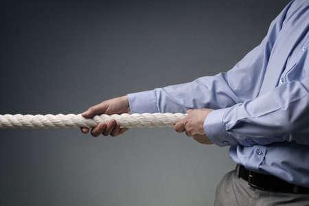 Los hombres de negocios que tiran de tira y afloja con un concepto de la cuerda de la competencia comercial, la rivalidad, desafío o controversia Foto de archivo