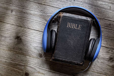 Holy Bible and headphones concept for modern religious education, podcast or help with hearing for blind studying
