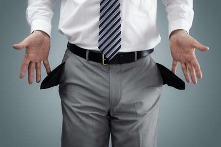 Businessman showing empty pockets concept for bankruptcy, poverty or penniless