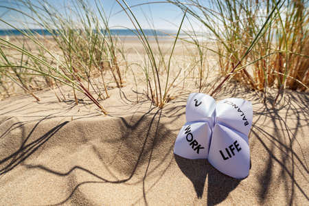 career job: Origami fortune teller on vacation at the beach concept for work life balance choices