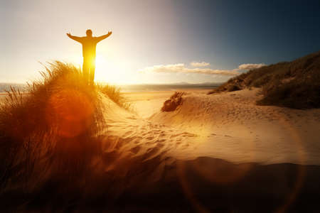 manos levantadas al cielo: Silueta de un hombre con las manos levantadas en la puesta de sol en una playa concepto de la religión, el culto, la oración y la alabanza