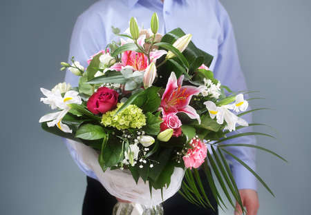 cut flowers: Businessman holding and giving a bouquet of flowers