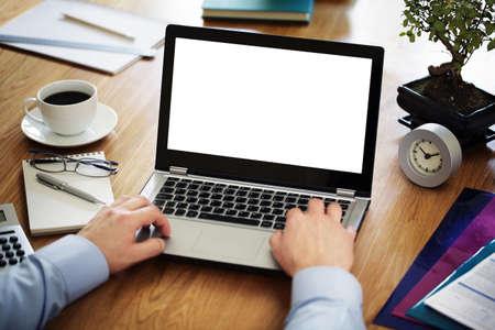 calculadora: Hombre de negocios en un escritorio en una oficina que pulsa en una computadora port�til con la pantalla en blanco blanco listo para el contenido Foto de archivo
