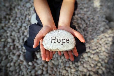 Dziecko na plaży z rękami ujął trzymając żwirowe z wygrawerowanym słowem nadziei koncepcji wiary, miłości, duchowości i religii