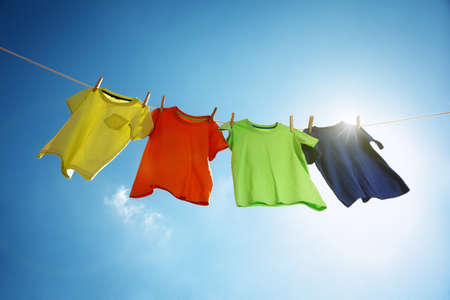 ropa colgada: Camisetas colgando de un tendedero en frente de cielo azul y el sol
