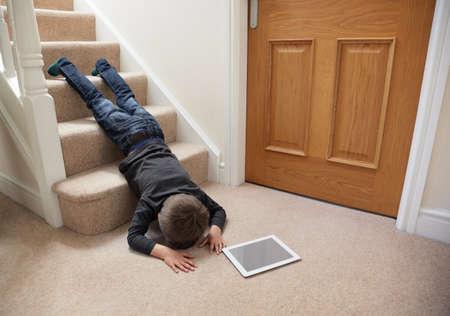 Niño caer por las escaleras, mientras que jugando en la tableta digital no concentrar concepto de seguridad en el hogar Foto de archivo