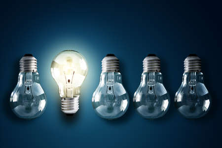 light bulb idea: Illuminated light bulb in a row of dim ones concept for creativity, innovation and solution Stock Photo