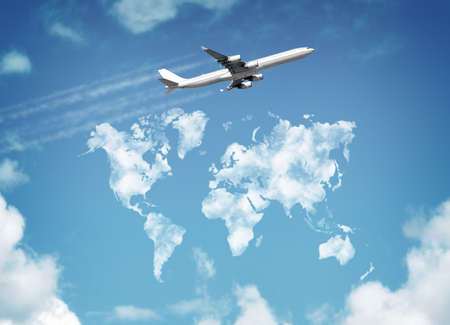 Passanger airplane flying above sky with clouds in shape of world map concept for travel and vacations