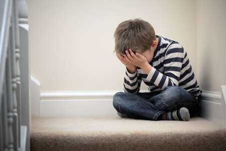 boys: Upset problem child with head in hands sitting on staircase concept for bullying, depression stress or frustration