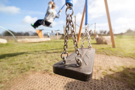 school playground: Empty playground swing with children playing in the background concept for child protection, abduction or loneliness