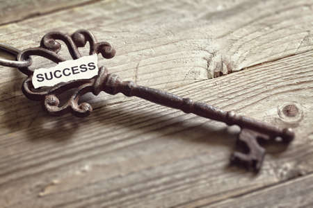 antique keys: Antique key with word success written on paper resting on wooden surface concept for aspirations and success