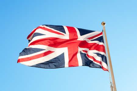 flag pole: British flag or union jack flying on a flag pole against a blue sky