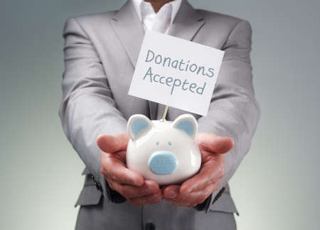 donating: Businessman holding piggy bank donation box for charity fundraising, investment or venture capitalist loan