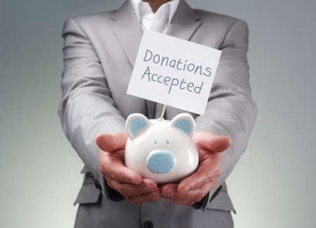Geschäftsmann mit Sparschwein Spendenbüchse für Spendenaktionen, Investitions- oder Risikokapitalgeber Kredit Standard-Bild
