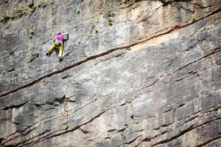 belaying: Rock climber stretching for hold on vertical climb with copy space Stock Photo